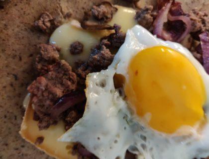 st nectaire fondu sur le steak recouvert d un oeuf au plat